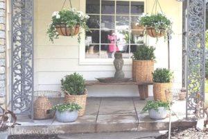 Porche delantero con cestas de boj, cubos galvanizados y plantas colgantes.